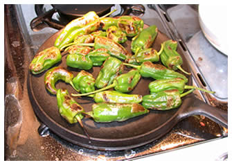 Roasting padron peppers on a comal
