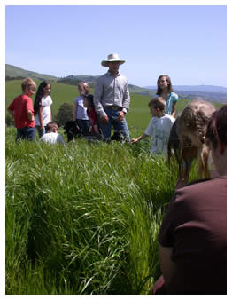 Joe and children in knee deep grass on Spring Field Day